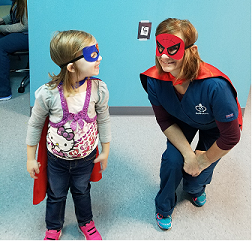 Therapist and girl dressed up as super heroes