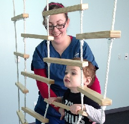 Therapist working with boy climbing rope ladder