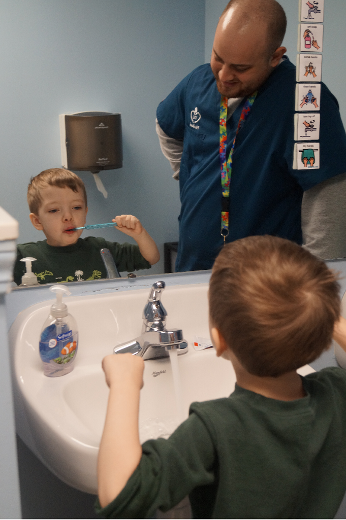 Boy learning to brush teeth with therapist