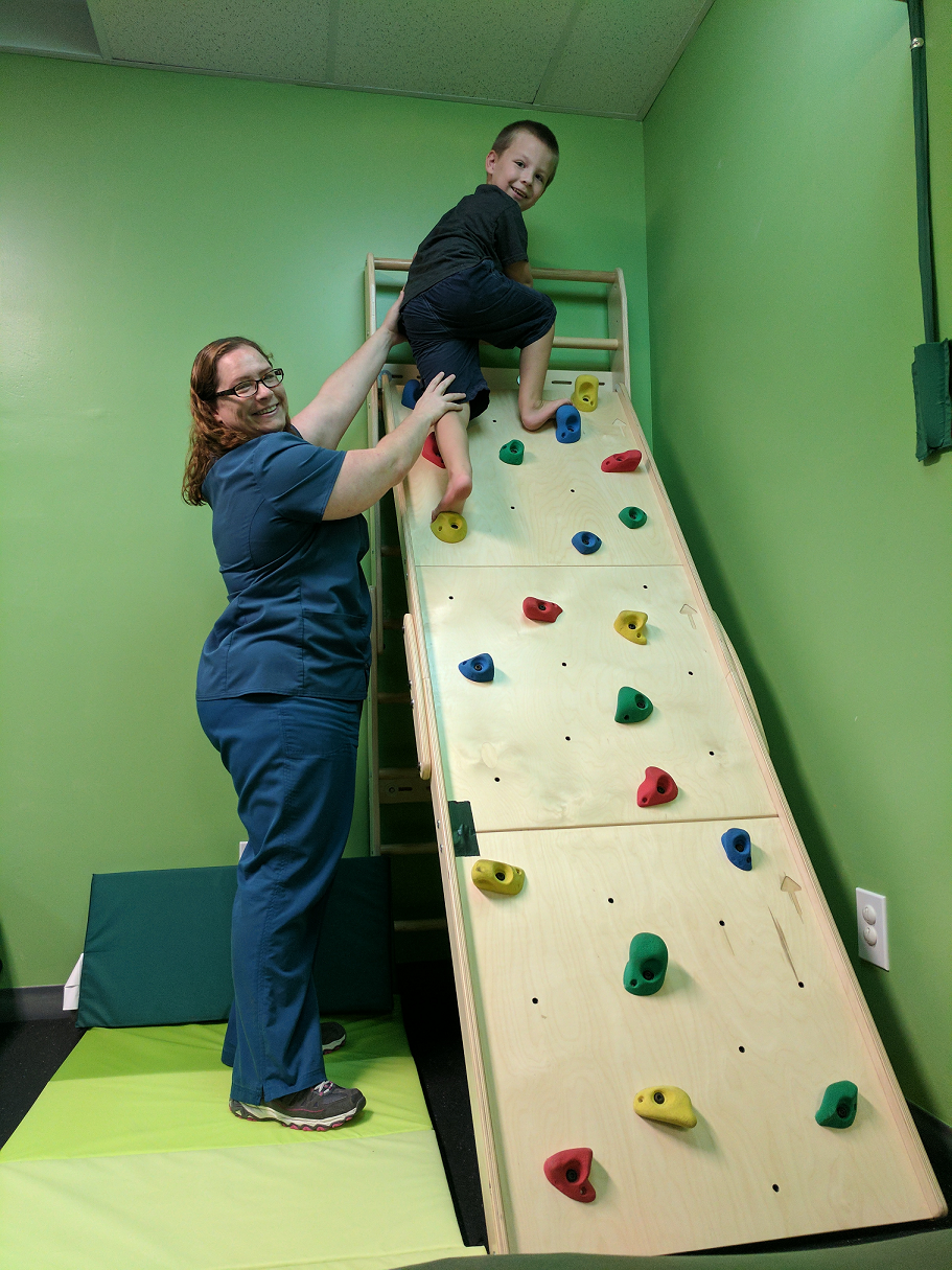 Therapist assisting boy on rock climbing wall
