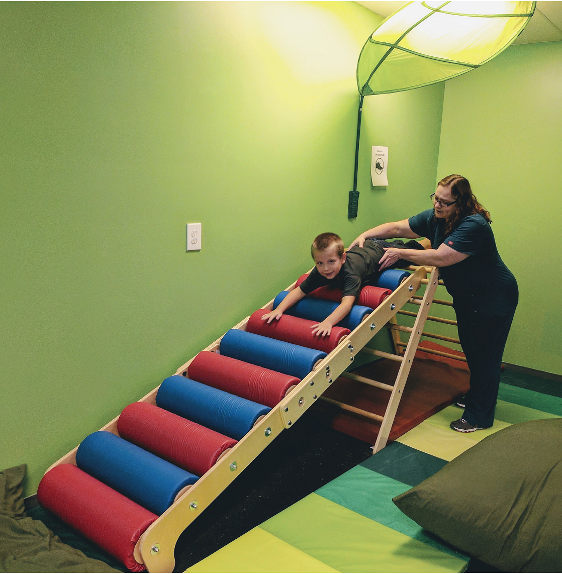 Therapist and boy going down roller slide
