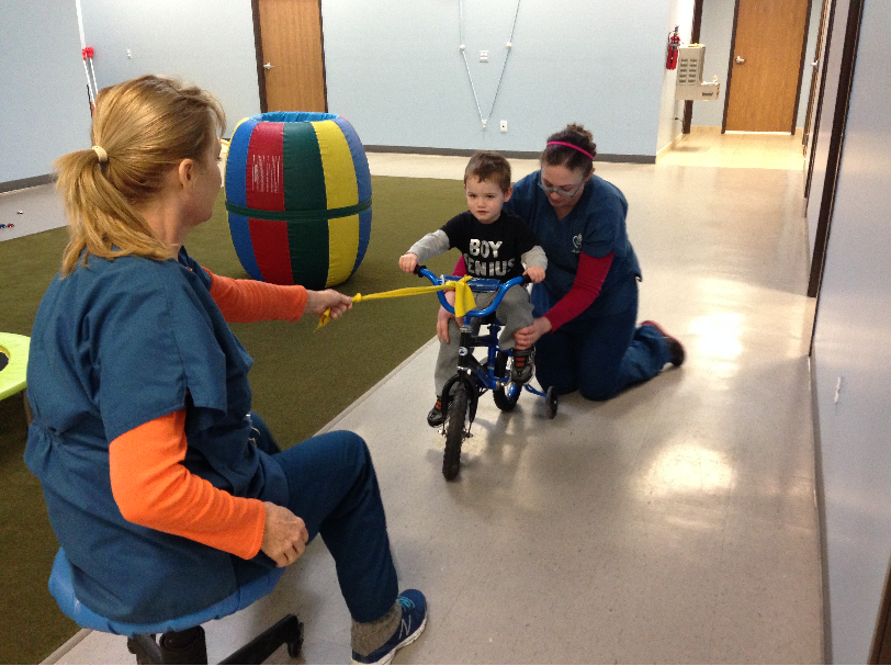 Boy learning to ride bike with therapists