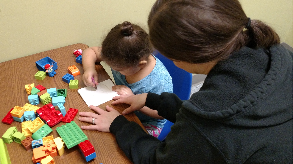 Therpist working with girl and blocks