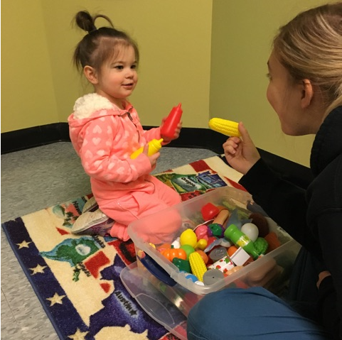 Therapist and girl identifying food toys