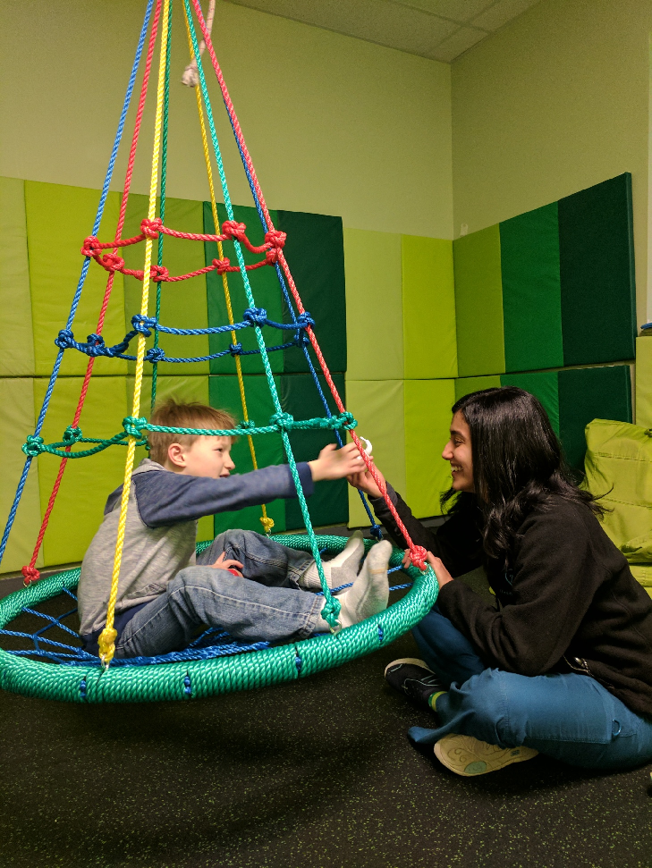 Therapist working with boy on web swing